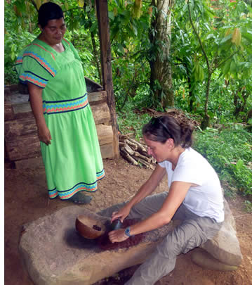 Tourist grinding cacao seeds under the watch of a Ngobe indigenous lady