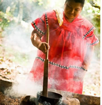 Indigenous women in traditional dress roasting cacao seeds